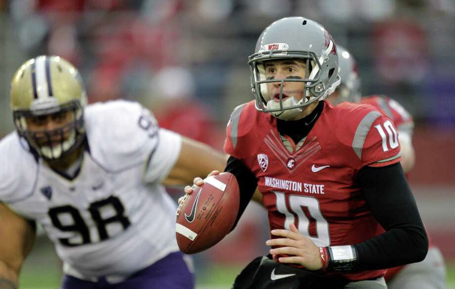 Washington State quarterback Jeff Tuel (10) looks to pass as Washington's Semisi Tokolahi (98) closes in during the second half. Photo: AP