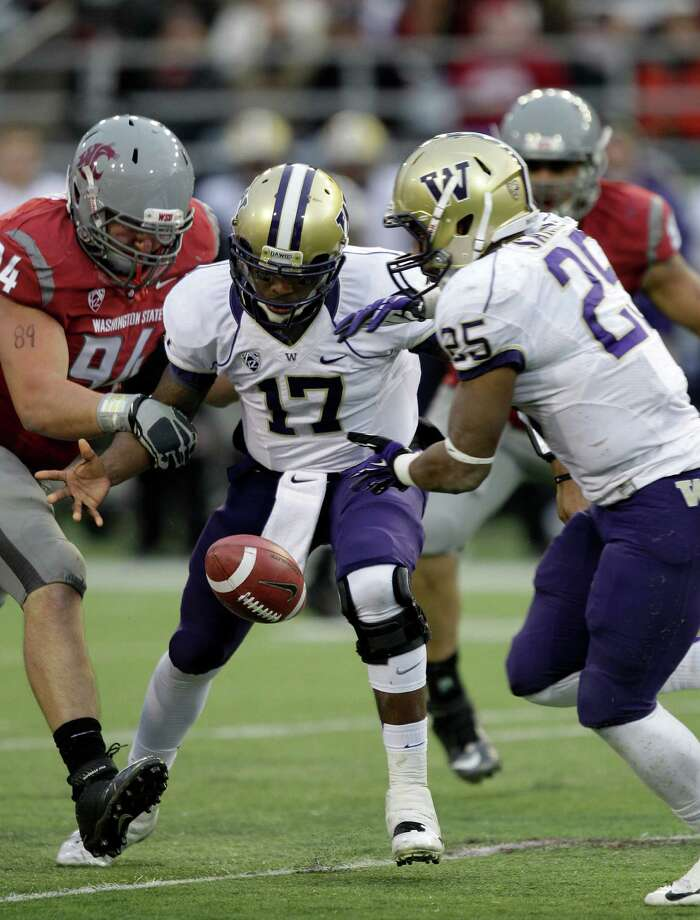 Washington quarterback Keith Price (17) fumbles next to Washington's Bishop Sankey, right, and Washington State's Steven Hoffart, left, in the second half. Photo: AP
