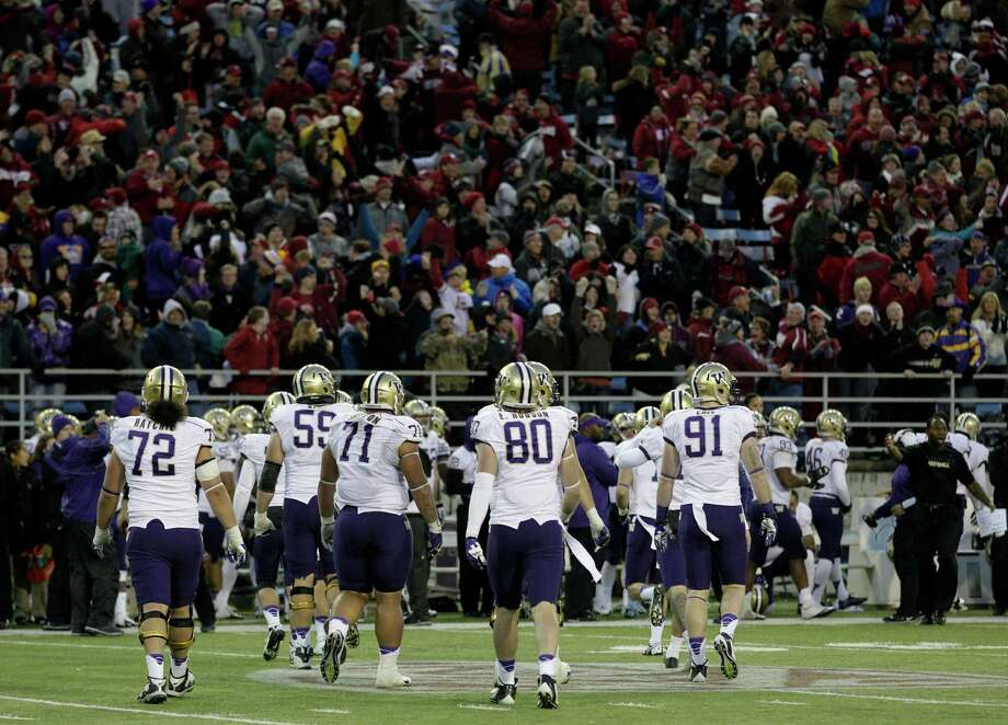 Washington football players leave the field at the end of the fourth quarter after Washington's Travis Coons missed a field goal to send the game into overtime. Photo: AP