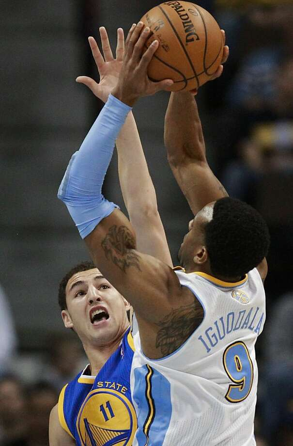 Golden State Warriors guard Klay Thompson (11) defends on a shot by Denver Nuggets guard Andre Iguodala (9) during the first quarter of an NBA basketball game Friday, Nov. 23, 2012, in Denver. (AP Photo/Barry Gutierrez) Photo: Barry Gutierrez, Associated Press