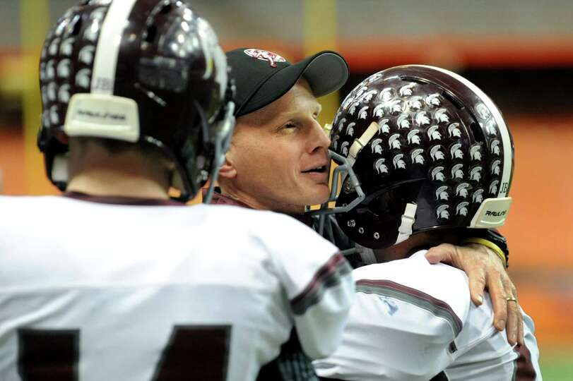 Burnt Hills' coach Matt Shell, center, embraces his players as the clock winds down in their Class A