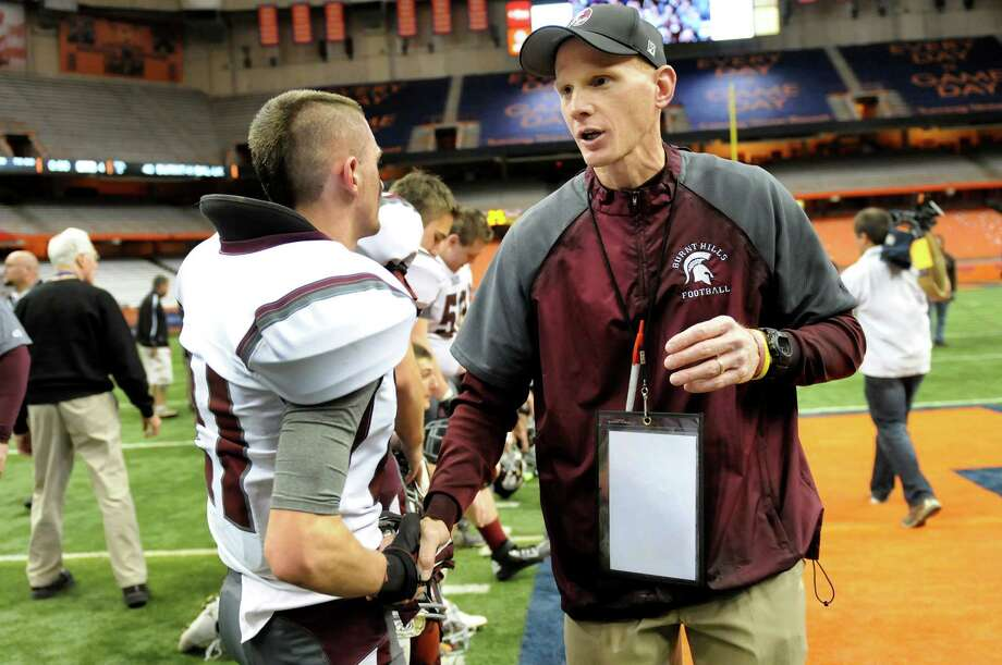 Burnt Hills' coach Matt Shell, center, congratulates each player, including Pau Rockwell (21), left, when they win 40-14 over Sweet Home in their Class A football state final on Friday, Nov. 23, 2012, at the Carrier Dome in Syracuse, N.Y. (Cindy Schultz / Times Union) Photo: Cindy Schultz /  00020203A