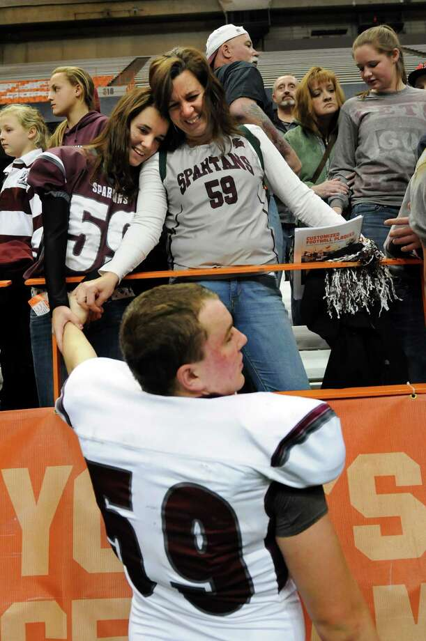 Burnt Hills' Shayne Briaddy (59), center, celebrates with his sister, Caroline, 13, left, and mother, Heather, when they win 40-14 over Sweet Home in their Class A football state final on Friday, Nov. 23, 2012, at the Carrier Dome in Syracuse, N.Y. (Cindy Schultz / Times Union) Photo: Cindy Schultz /  00020203A
