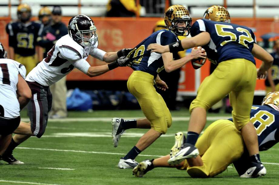 Burnt Hills' Paul Krowel (89), left, gets ahold of Sweet Home's quarterback Michael Torrillo (10) for a sack during their Class A football state final on Friday, Nov. 23, 2012 at the Carrier Dome in Syracuse, N.Y. (Cindy Schultz / Times Union) Photo: Cindy Schultz /  00020203A