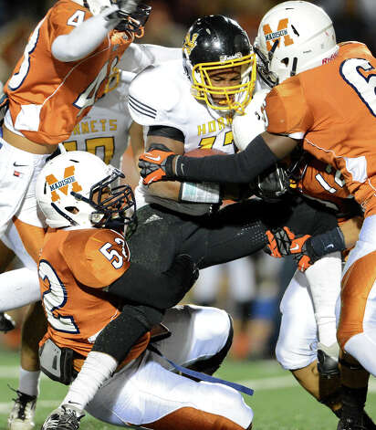 East Central's Johnathan Jackson is tackled by a group of Madison defenders during a Class 5A Division I second round playoff game at Comalander Stadium in San Antonio, Friday, November 23, 2012.