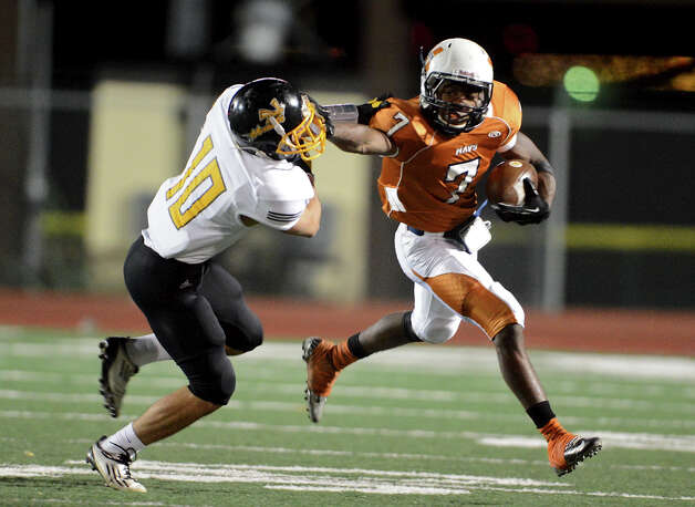 Madison's Marquis Warford (7) gives a stiff-arm to East Central's Dustin Toscano (10) during a Class 5A Division I second round playoff game at Comalander Stadium in San Antonio, Friday, November 23, 2012.