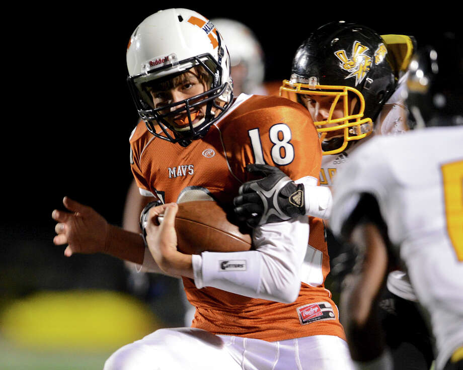 Madison quarterback Tyler Mangold (18) is wrapped up from behind by an East Central defender during a Class 5A Division I second round playoff game at Comalander Stadium in San Antonio, Friday, November 23, 2012.