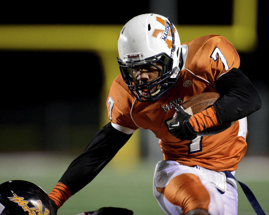 Madison's Marquis Warford (7) tries to avoid an East Central defender during a Class 5A Division I second round playoff game at Comalander Stadium in San Antonio, Friday, November 23, 2012.