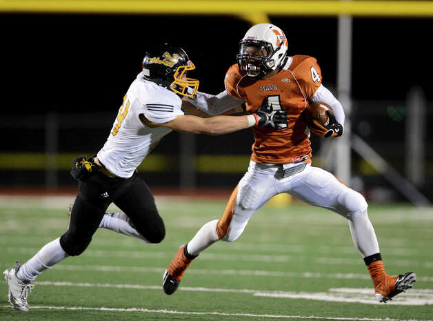 Madison's Byron Daniels (4) tries to get away from East Central's Russell Brown (14) during a Class 5A Division I second round playoff game at Comalander Stadium in San Antonio, Friday, November 23, 2012.