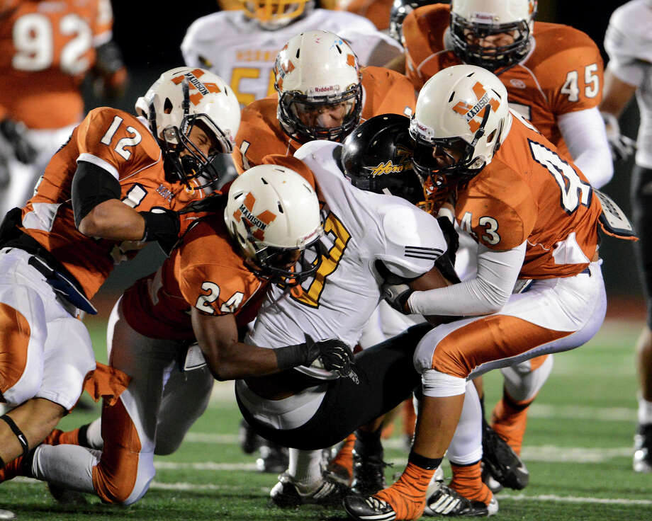 A group of Madison defenders tackles East Central's Johnathan Jackson (13) during a Class 5A Division I second round playoff game at Comalander Stadium in San Antonio, Friday, November 23, 2012. John Albright / Special to the Express-News. Photo: JOHN ALBRIGHT, Express-News / San Antonio Express-News