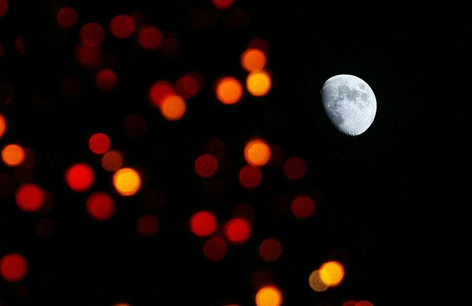 A gibbous moon is seen through some lights at the holiday display at Temple Square in Salt Lake City on Friday, Nov. 23, 2012. Photo: Scott Sommerdorf, Associated Press