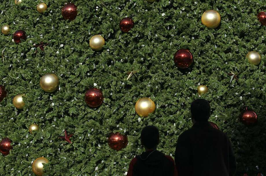 Two shoppers walk past the large Macy's Tree at Union Square in San Francisco, Friday, Nov. 23, 2012. Black Friday, the day when retailers traditionally turn a profit for the year, got a jump start this year as many stores opened just as families were finishing up Thanksgiving dinner. Photo: Jeff Chiu, Associated Press