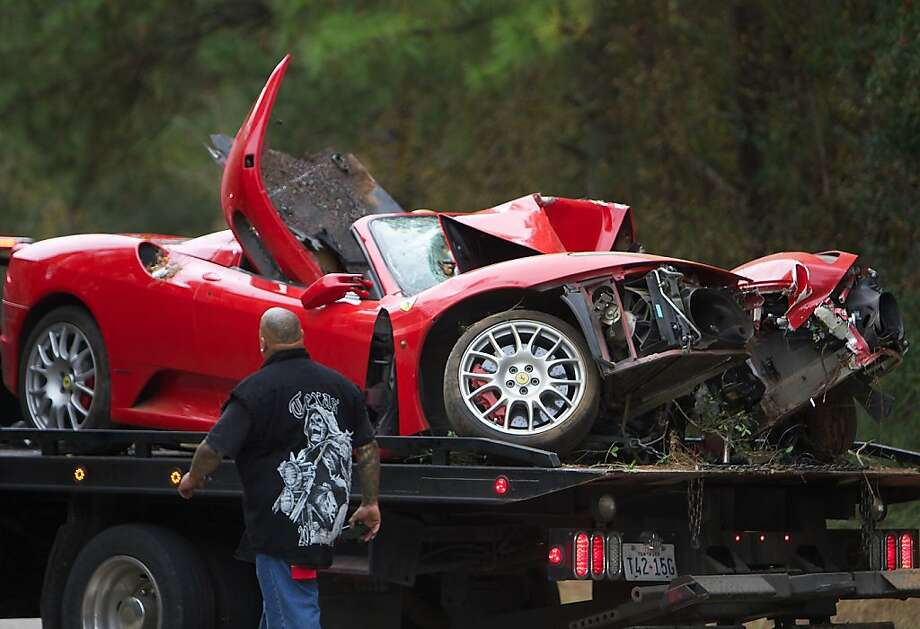 A truck driver looks at a damaged Ferrari convertible which was involved in a single-vehicle accident Friday, Nov. 23, 2012 after it crashed into a wooded area in Conroe, Texas. The driver of the sportscar was not seriously injured and was transported via ambulance to Conroe Regional Hospital. Photo: Eric Swist, Associated Press
