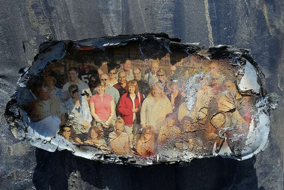 A fire and flood-damaged photo is displayed after it was salvaged by Deirdre Mathis McGovern, from the ashes of her parents' home in the Breezy Point section of the Queens borough of New York, Friday, Nov. 23, 2012. A fire destroyed more than 100 homes in the oceanfront community during the storm. Photo: Mark Lennihan, Associated Press