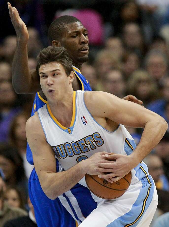Denver Nuggets forward Danilo Gallinari (8) drives past Golden State Warriors center Festus Ezeli during the first quarter of an NBA basketball game Friday, Nov. 23, 2012, in Denver. (AP Photo/Barry Gutierrez) Photo: Barry Gutierrez, Associated Press