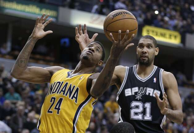 Indiana Pacers' Paul George (24) grabs a rebound in front of San Antonio Spurs' Tim Duncan during the first half of an NBA basketball game Friday, Nov. 23, 2012, in Indianapolis. (Darron Cummings / Associated Press)