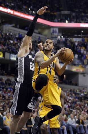 Indiana Pacers' D.J. Augustin puts up a shot against San Antonio Spurs' Tiago Splitter during the first half of an NBA basketball game Friday, Nov. 23, 2012, in Indianapolis.  (Darron Cummings / Associated Press)