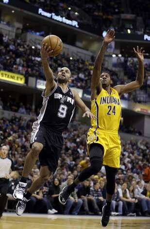 San Antonio Spurs' Tony Parker puts up a shot against Indiana Pacers' Paul George during the second half of an NBA basketball game Friday, Nov. 23, 2012, in Indianapolis. The Spurs won 104-97.  (Darron Cummings / Associated Press)