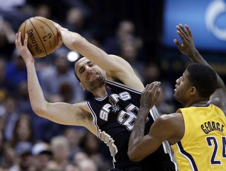 San Antonio Spurs' Manu Ginobili, left, keeps the ball from Indiana Pacers' Paul George during the second half of an NBA basketball game Friday, Nov. 23, 2012, in Indianapolis. The Spurs won 104-97. (Darron Cummings / Associated Press)