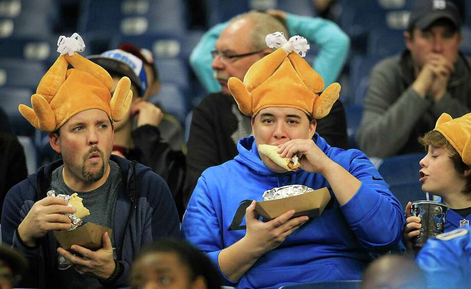 Lions fans wear turkey hats fans as they eat  before the game. Photo: Karen Warren, Houston Chronicle / © 2012  Houston Chronicle