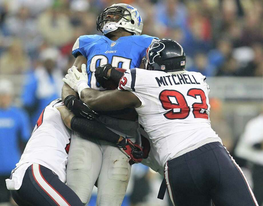 Lions tight end Brandon Pettigrew (87) gets hit hard by Texans nose tackle Earl Mitchell (92) during the third quarter. Photo: Karen Warren, Houston Chronicle / © 2012  Houston Chronicle