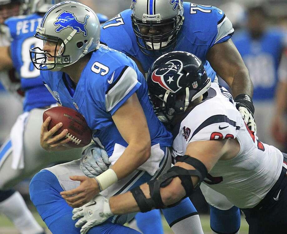 Texans defensive end J.J. Watt  sacks Detroit quarterback Matthew Stafford on the first play of the first quarter. Photo: Karen Warren, Houston Chronicle / © 2012  Houston Chronicle
