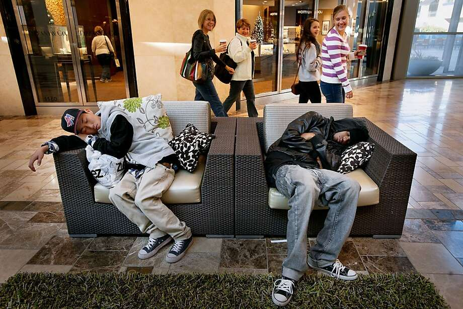 Sam Choi, left foreground, and Matt Nunley sleep while shoppers, Kim Dowling, left, Karen Kamilos, Dowlinng's daughter Nicole Zahner, 15, and Kamilos' daughter Julia Kamilos, 15, laugh as they pass them by at the Westfield Galleria in Roseville on Friday, November 23, 2012. (Randall Benton/Sacramento Bee/MCT) Photo: Randall Benton, McClatchy-Tribune News Service