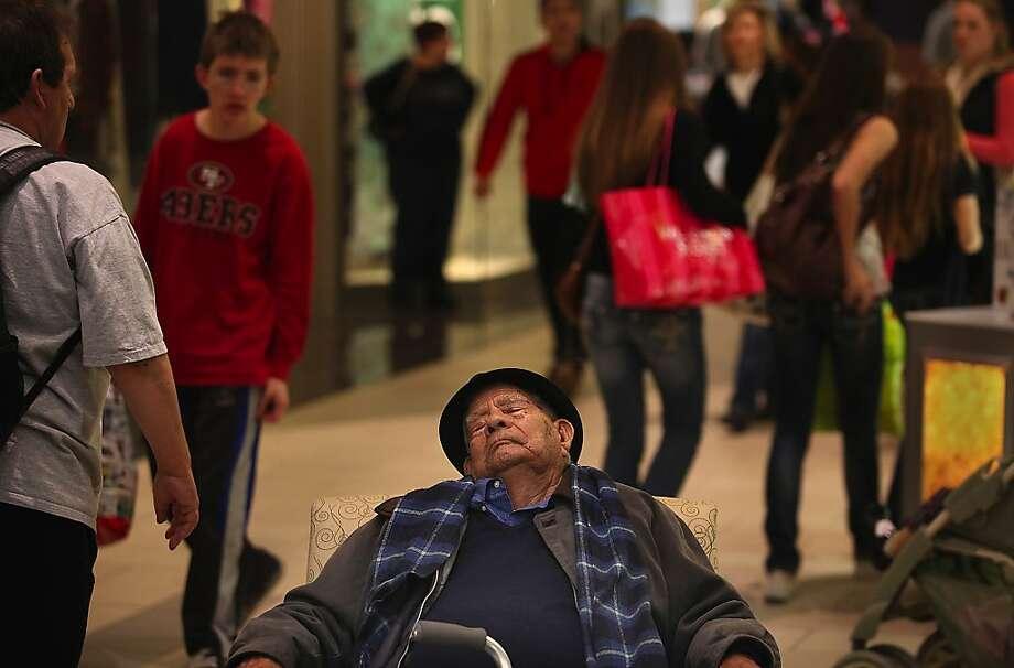 Enrique Mendez of Santa Rosa slumbers as he waits for a relative to finish shopping at the Santa Rosa Plaza, Black Friday, Nov. 23, 2012 in Santa Rosa.  (AP Photo/Kent Porter, Press Democrat) Photo: Kent Porter, Associated Press