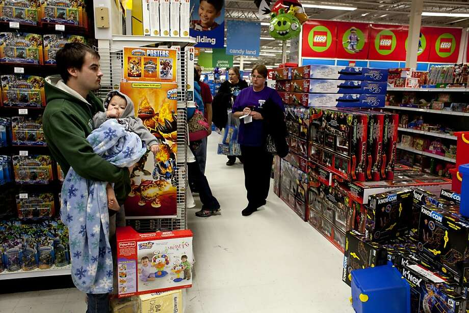Shoppers gather goods in Saginaw Township, Mich., on Friday, Nov. 23, 2012. Black Friday, the day when retailers traditionally turn a profit for the year, got a jump start this year as many stores opened just as families were finishing up Thanksgiving dinner.(AP Photo/The Saginaw News, Jon Garcia) ALL LOCAL TV OUT; LOCAL TV INTERNET OUT Photo: Jon Garcia | MLive.com, Associated Press