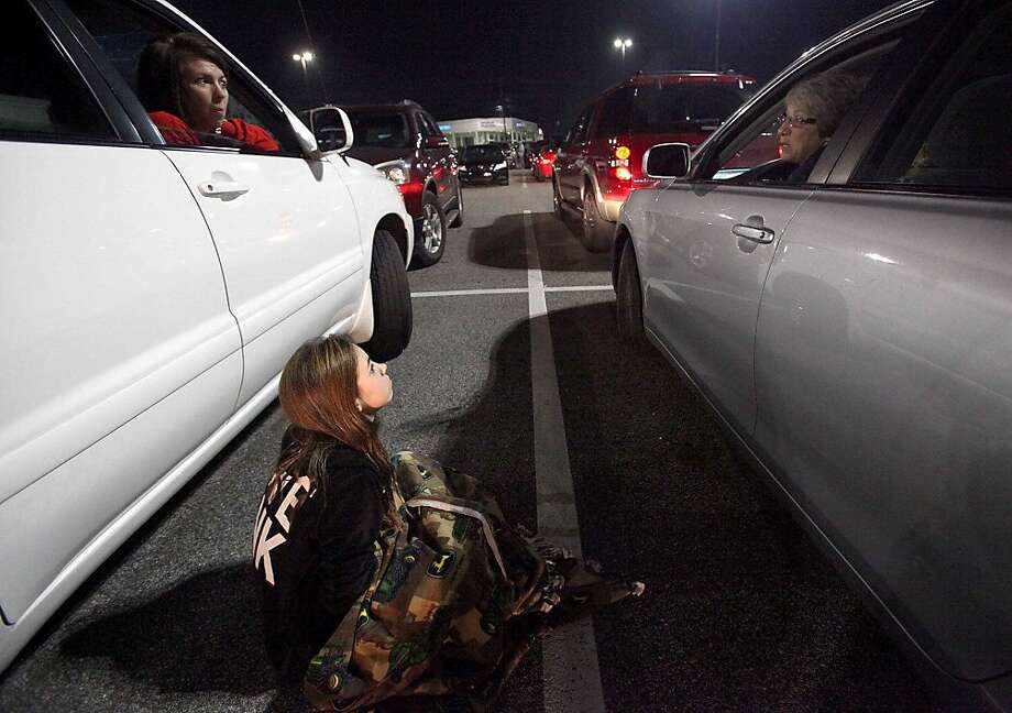 Emily Brewer sits on the ground between her mother, Kandie Brewer, left, and Diane Martin as they wait in their cars for a store to open for Black Friday shopping in Tuscaloosa, Ala. on Friday, Nov. 23, 2012. (AP Photo/The Tuscaloosa News, Dusty Compton) Photo: Dusty Compton, Associated Press