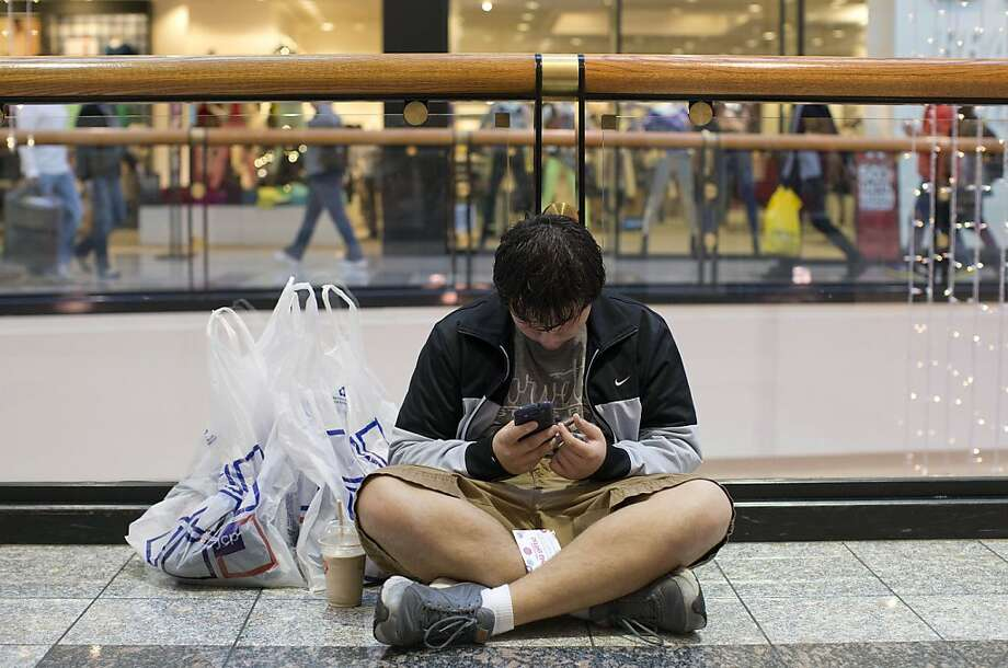 A 16-year-old boy who identified himself only as Dominic checks out a coupon offer from J.C. Penney on his cell phone while waiting for his mother to finish shopping at a mall, Friday, June 23, 2012, in Las Vegas. Black Friday, the day when retailers traditionally turn a profit for the year, got a jump start this year as many stores opened just as families were finishing up Thanksgiving dinner. (AP Photo/Julie Jacobson) Photo: Julie Jacobson, Associated Press