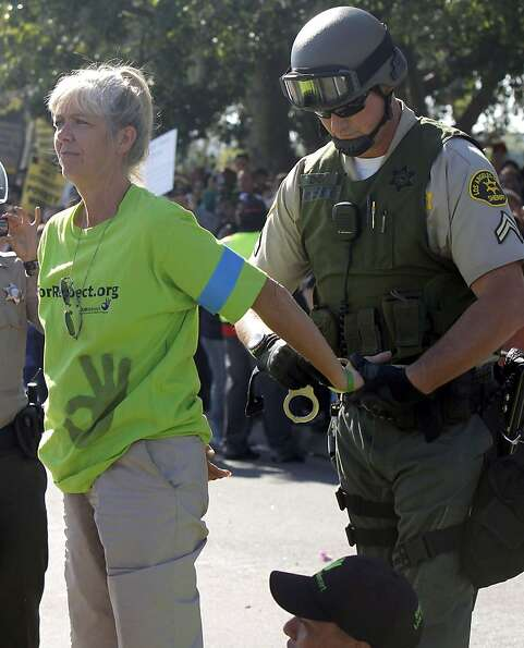 A protester is detained by police outside a Walmart in Paramount (Los Angeles County). Demonstration