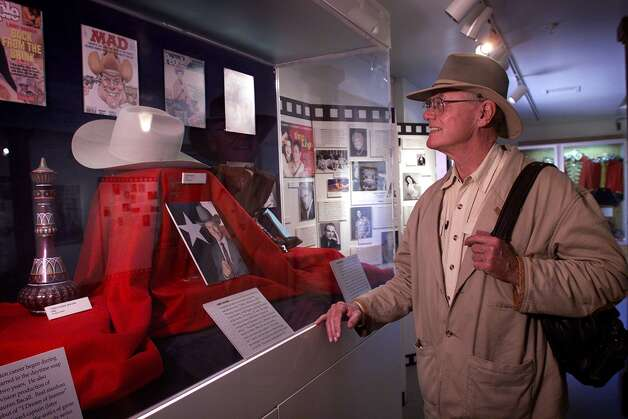 "Hagman takes a look at a display of props from ""Dallas"" AND ""I Dream of Jeannie"" in California in 2000."