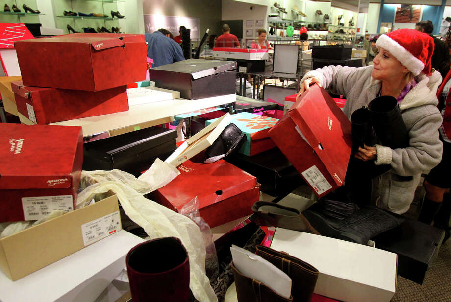 Rose Pena (right) sifts through a pile of shoe boxes looking for a boot that matches the one she was hoping to purchase at JC Penny at North Star Mall Black Friday November 23, 2012. Pena and other shoppers at the mall were taking advantage of Black Friday sales. Photo: JOHN DAVENPORT, San Antonio Express-News / ©San Antonio Express-News/Photo Can Be Sold to the Public