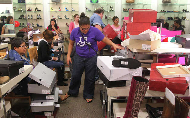 Raulene Flores (center) sifts through a pile of shoe boxes looking for some boots for her mother at JC Penny at North Star Mall Black Friday November 23, 2012. Flores and other shoppers at the mall were taking advantage of Black Friday sales. Photo: John Davenport, San Antonio Express-News / San Antonio Express-News