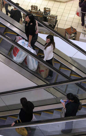 Shoppers take the escalators at JC Penny at North Star Mall Black Friday Nov. 23, 2012. A local economist said Thursday that San Antonio's shoppers are growing more confident as the city's economic base expands, factors that are harbingers of an improving metro economy and of higher wages in a city that's long been known as a low-wage town. Photo: John Davenport, San Antonio Express-News / San Antonio Express-News