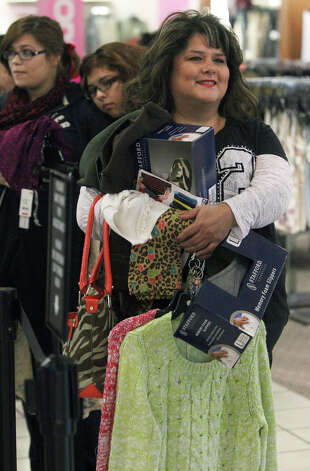 Kathleen Barbknecht clutches merchandise while waiting in line to pay at JC Penny at North Star Mall Black Friday November 23, 2012. Photo: John Davenport, San Antonio Express-News / San Antonio Express-News