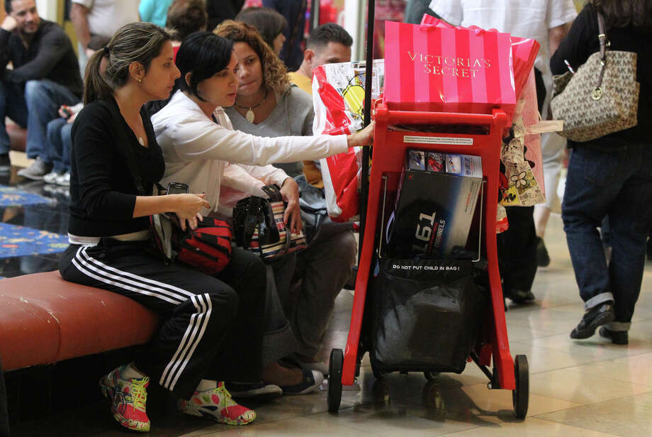 Clorimar Rodriguez (left), Lauryn Rengifo (center) and Lismaren Bejarano (right) look through merchandise they purchased on Black Friday November 23, 2012 while shopping at North Star Mall. The three women are from Caracas, Venezuela and said they are on vacation here. Photo: John Davenport, San Antonio Express-News / San Antonio Express-News