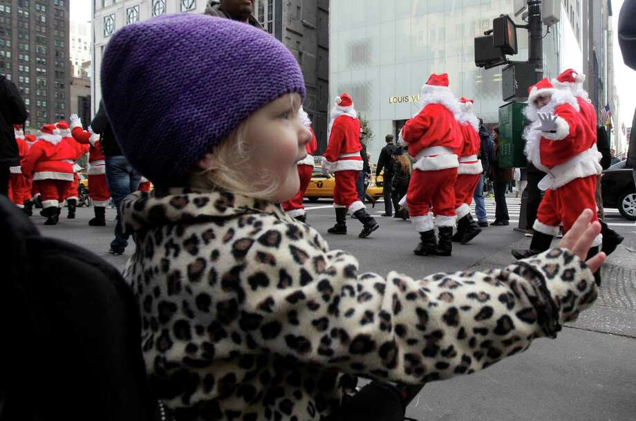 A young girls waves at Volunteers of America Santas during their 110th annual Sidewalk Santa Parade, on New York's Fifth Ave., Friday, Nov. 23, 2012. The donations they raise are used for a holiday food voucher program for needy residents. Photo: Richard Drew, AP / AP