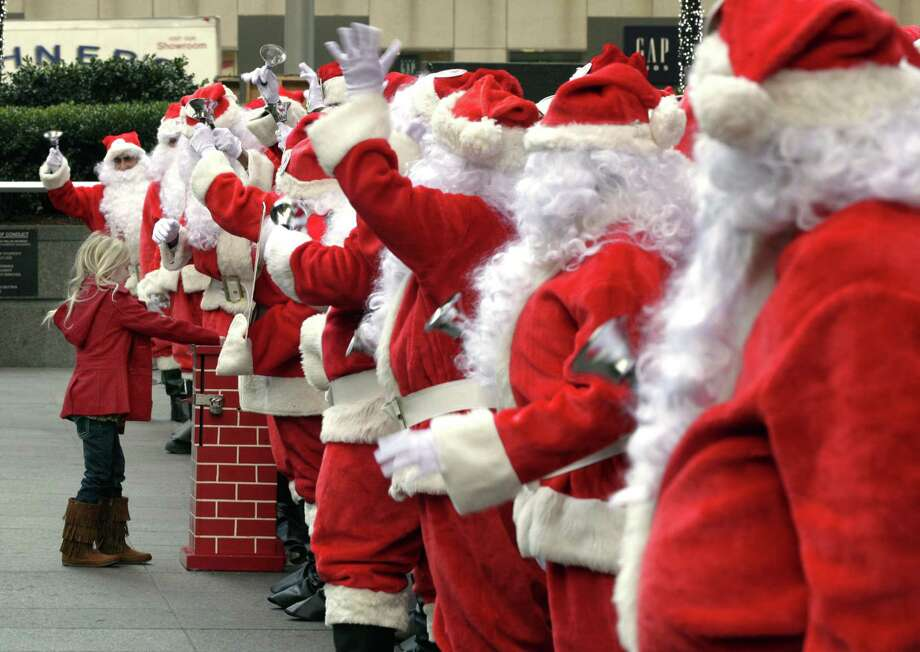 A young girl makes a donation to the Volunteers of America Santas during their 110th annual Sidewalk Santa Parade, in New York,  Friday, Nov. 23, 2012. The donations they raise are used for a holiday food voucher program for needy residents. Photo: Richard Drew, AP / AP