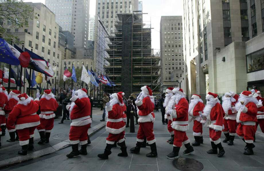 Volunteers of America Santas walk past the Rockefeller Center Christmas tree during their 110th annual Sidewalk Santa Parade, in New York,  Friday, Nov. 23, 2012. The donations they raise are used for a holiday food voucher program for needy residents. Photo: Richard Drew, AP / AP