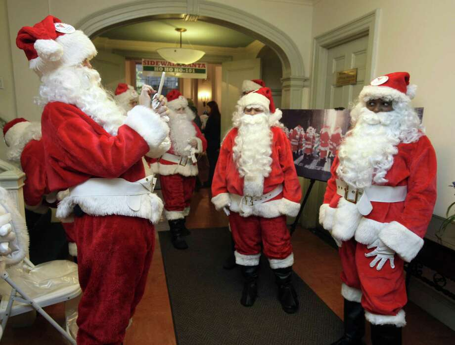 Volunteers of America Santas pose for photos before their the 110th annual Sidewalk Santa Parade, in New York,  Friday, Nov. 23, 2012. The donations they raise are used for a holiday food voucher program for needy residents. Photo: Richard Drew, AP / AP