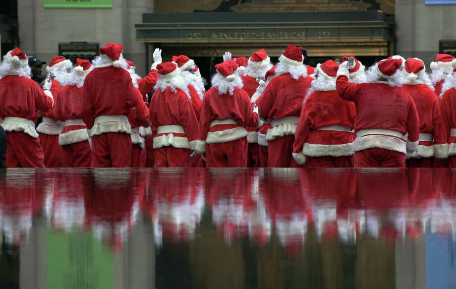 Volunteers of America Santas are reflected in a fountain during their 110th annual Sidewalk Santa Parade, in New York,  Friday, Nov. 23, 2012. The donations they raise are used for a holiday food voucher program for needy residents. Photo: Richard Drew, AP / AP