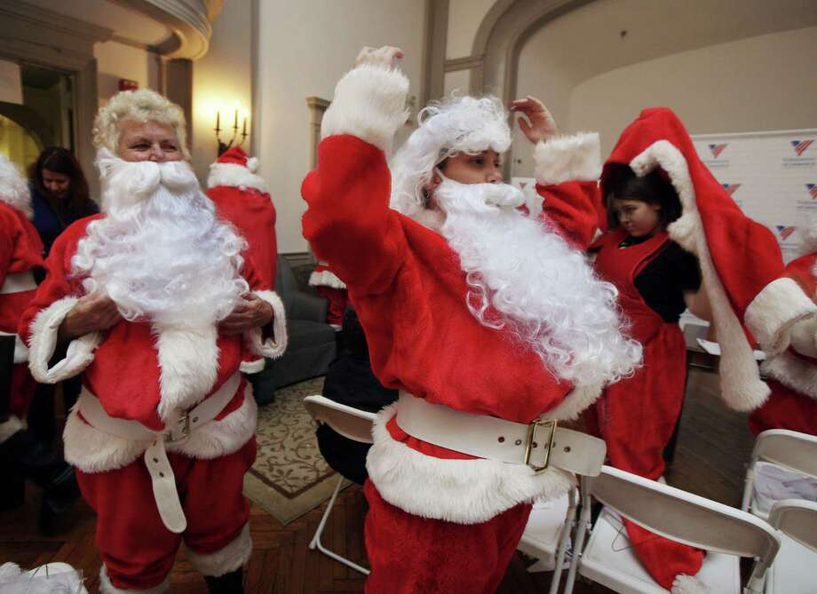 Kathy Trezza, left  and her daughter Kathryn Trezza, suit up at Volunteers of America headquarters for the 110th annual Sidewalk Santa Parade, in New York,  Friday, Nov. 23, 2012. The donations they raise are used for a holiday food voucher program for needy residents. Photo: Richard Drew, AP / AP