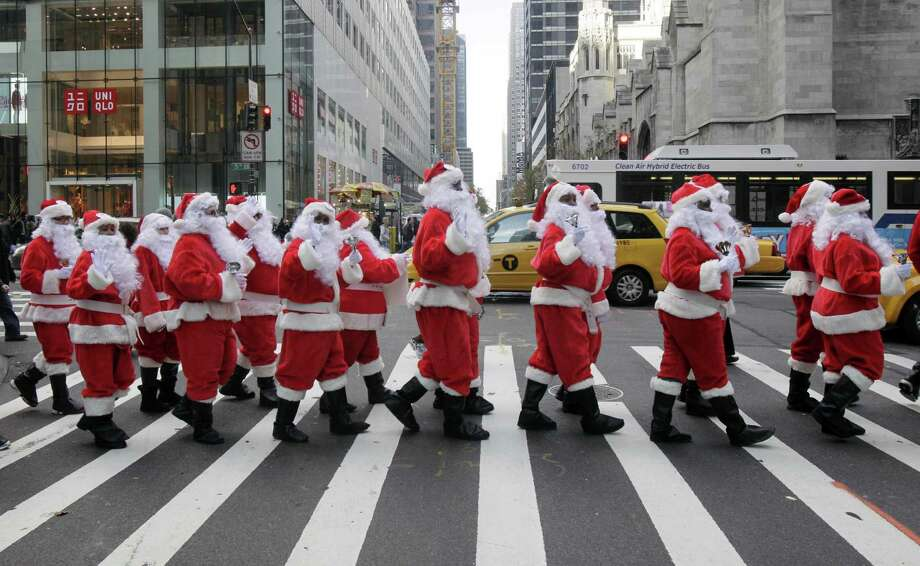 Volunteers of America Santas ring their bells as the cross a street in Fifth Ave. during their 110th annual Sidewalk Santa Parade, in New York,  Friday, Nov. 23, 2012. The donations they raise are used for a holiday food voucher program for needy residents. Photo: Richard Drew, AP / AP