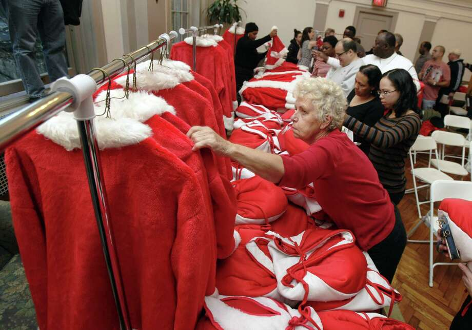 Kathy Trezza, foreground, chooses her outfit at Volunteers of America headquarters in New York, as she prepares for the 110th annual Sidewalk Santa Parade, Friday, Nov. 23, 2012. The donations they raise are used for a holiday food voucher program for needy residents. Photo: Richard Drew, AP / AP