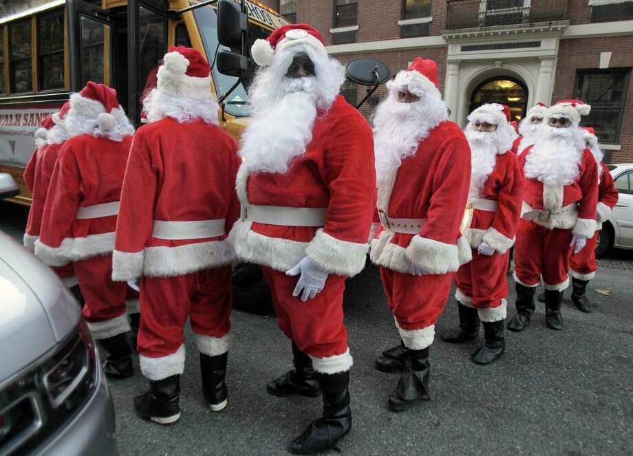 Volunteers of America Santas board a school bus to the start of the 110th annual Sidewalk Santa Parade, in New York,  Friday, Nov. 23, 2012. The donations they raise are used for a holiday food voucher program for needy residents. Photo: Richard Drew, AP / AP