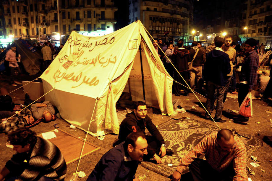 "In this Friday Nov. 23, 2012 photo, Egyptian pro-democracy demonstrators occupy Tahrir Square, birthplace of the Arab Spring, in Cairo, Egypt. The unrest underscored the struggle over the direction of Egypt's turbulent passage nearly two years after a popular uprising toppled Hosni Mubarak's authoritarian regime. Liberals and secular Egyptians accuse the Brotherhood of monopolizing power, dominating the writing of a new constitution and failing to tackle the country's chronic economic and security problems. Arabic writing on tent reads, "" Egypt is not a farm, Constitution party, Egypt for Egyptians."" Photo: Uncredited, AP / AP"