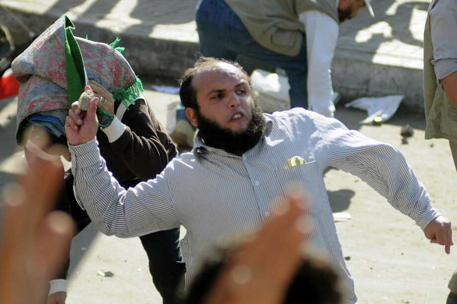 TOPSHOTS  Egyptian supporters and opponents of President Mohamed Morsi clash in the Mediterranean coastal city of Alexandria on November 23, 2012. Opponents set fire to Muslim Brotherhood offices in three Egyptian cities, state television reported, as rival rallies gathered nationwide a day after Morsi assumed sweeping powers. AFP PHOTO / STR-/AFP/Getty Images Photo: -, AFP/Getty Images / AFP