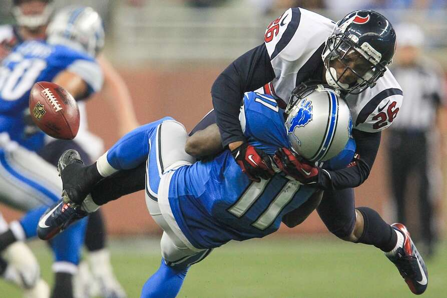 Texans defensive back Brandon Harris (26) hits Lions wide receiver Stefan Logan (11) hard on a kicko